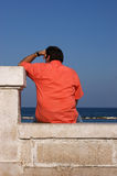 Thoughtful man looking at the sea. Thoughtful man wearing a salmon shirt sat in front of the sea Royalty Free Stock Images