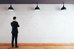 Thoughtful man looking at wall. Thoughtful businessman looking at blank brick wall in room with wooden floor and ceiling with lamps. Mock up, 3D Rendering Royalty Free Stock Photos