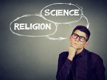 Thoughtful man making up his mind science or religion stock images
