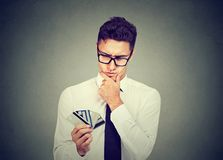 Thoughtful man with many different credit loyalty discount cards stock photography