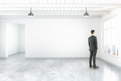 Thoughtful man near blank wall. Thoughtful businessman in empty room interior with blank concrete wall, floor, ceiling and window with city view. Mock up, 3D Royalty Free Stock Images
