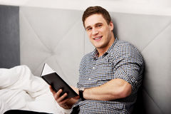 Thoughtful man with a note in his bed. Stock Photos