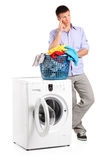 Thoughtful man posing next to a washing mashine Royalty Free Stock Photos