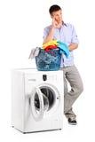 Thoughtful man posing next to a washing mashine Royalty Free Stock Photos