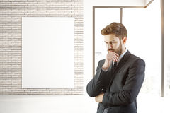 Thoughtful man and poster in interior. Thoughtful businessman in brick interior with empty banner, city view and daylight. Mock up, 3D Rendering Royalty Free Stock Photos