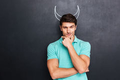 Thoughtful man pretending devil standing over chalkboard with drawn horns Royalty Free Stock Photography