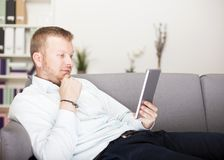 Thoughtful man reading his tablet computer Royalty Free Stock Photography