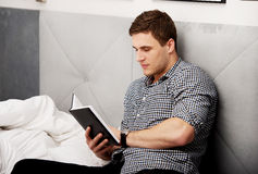 Thoughtful man reading a note in his bed. Stock Photo