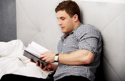 Thoughtful man reading a note in his bed. Royalty Free Stock Photo