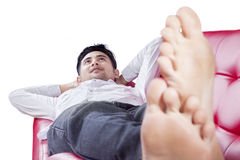 Thoughtful man relaxing on couch Royalty Free Stock Images