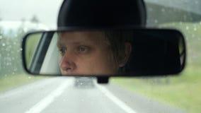 Thoughtful man riding in car through mountains during rainy day Stock Photos