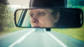 Thoughtful man riding in car through mountains during rainy day Stock Photography