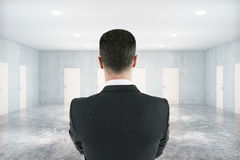 Thoughtful man in room with doors Royalty Free Stock Image