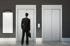Thoughtful man in room with lift. Thoughtful businessman standing in concrete office hall interior with lift and empty poster. Mock up, 3D Rendering Royalty Free Stock Photos