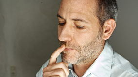 Thoughtful man rubbing his chin Royalty Free Stock Images