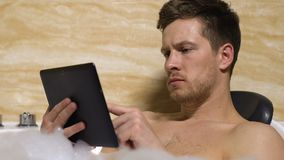 Thoughtful man scrolling tablet in bath, freelancer answering mail business tool. Stock footage stock video