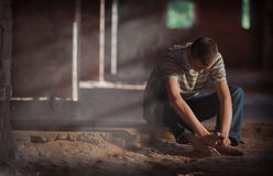 Man sitting on sandy floor. Thoughtful young man sitting on sandy floor  with his head cast down as if thinking deeply or depressed Royalty Free Stock Photo