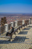Thoughtful man sitting on the bench. Older thoughtful man sitting on the bench on the tower of Vršac, Serbia, enjoying the view of the city royalty free stock photo