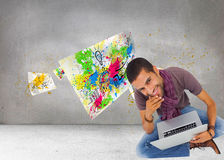 Thoughtful man sitting on floor using laptop and smiling at camera Stock Photography
