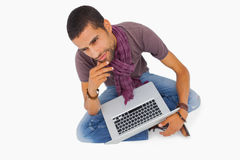 Thoughtful man sitting on floor using laptop Royalty Free Stock Photography