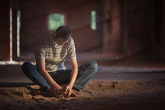 Thoughtful man sitting in building. Thoughtful multiracial young man sitting on sand in old house or building Royalty Free Stock Photo