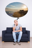 Thoughtful man sitting on sofa and dreaming about vacation Royalty Free Stock Photos