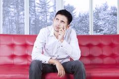 Thoughtful man sitting on sofa Royalty Free Stock Photo