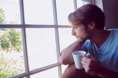 Thoughtful man sitting by the window having coffee Royalty Free Stock Photo