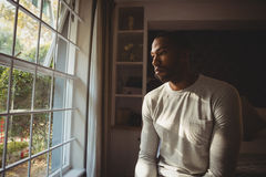 Thoughtful man sitting by window at home Stock Images