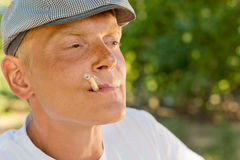 Thoughtful man smoking recalling good memories Stock Photography