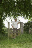 Thoughtful Man Standing Across Field Gate Stock Image