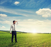 Thoughtful man standing on green field Stock Images