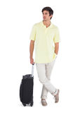 Thoughtful man standing with his suitcase Stock Images