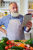Thoughtful man standing in the kitchen searching for recipe with Royalty Free Stock Photos