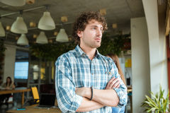 Thoughtful man standing in office with folded hands Stock Images