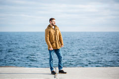 Thoughtful man standing on pier near the sea Stock Photos