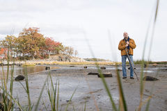 Thoughtful man standing with a stick Stock Image