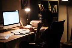 Thoughtful man studying using computer in dark room at home Stock Image