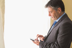 Thoughtful man texting on his mobile phone Royalty Free Stock Image