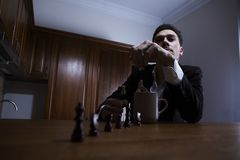 Thoughtful man throwing chess in the cup. Royalty Free Stock Photo