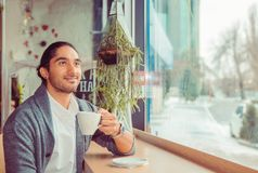 Thoughtful man at trendy coffee shop looking up daydreaming stock photos