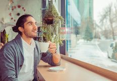 Thoughtful man at trendy coffee shop looking up daydreaming royalty free stock photo