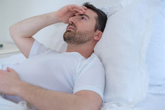 Thoughtful man trying to sleep in bed at night Stock Image
