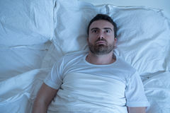 Thoughtful man trying to sleep in his bed at night Royalty Free Stock Image