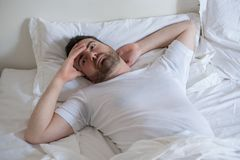 Upset man trying to sleep in his bed at night. Thoughtful man trying to sleep in his bed at night Royalty Free Stock Photos