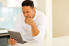 Thoughtful man using tablet Royalty Free Stock Image