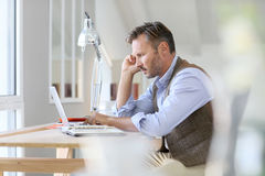 Thoughtful man working at home on laptop Royalty Free Stock Photos