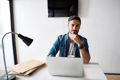 Thoughtful man working in office royalty free stock photography