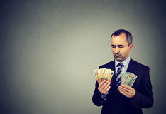Thoughtful business man looking at euro and dollar cash banknotes Royalty Free Stock Image