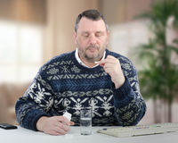 Thoughtful mature man looking at the white pill Royalty Free Stock Photography